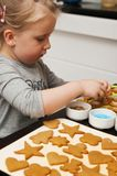 Little girl decorating Christmas cookies Stock Photos