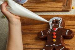 Little girl decorating of christmas gingerbread cookie Royalty Free Stock Image