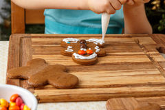 Little girl decorating of christmas gingerbread cookie Stock Photography