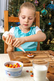Little girl decorating of christmas gingerbread cookie Stock Photo