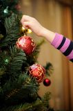 Little girl decorating the Christmas tree. (focus on ball Royalty Free Stock Photography