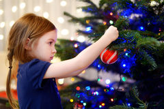 Little girl decorating a Christmas tree. Adorable little girl decorating a Christmas tree with colorful glass baubles at home Royalty Free Stock Images