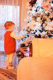 Little girl decorating christmas tree Stock Photos