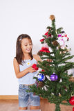 Little girl decorating a christmas tree Royalty Free Stock Image
