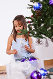 Little girl decorating a christmas tree Royalty Free Stock Photos
