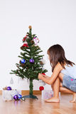 Little girl decorating a christmas tree Stock Images