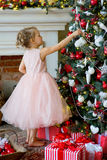 Little girl decorating Christmas tree at home Stock Images