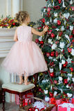 Little girl decorating Christmas tree at home Stock Photos
