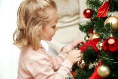 Little girl decorating christmas tree at home Royalty Free Stock Images