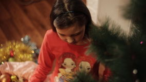 Little girl decorating Christmas tree at home. Little girls in comfortable home clothes sitting on floor in beautiful Christmas decorations. Two little sisters stock footage