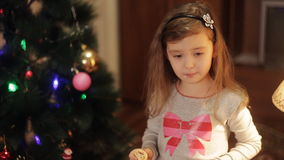 Little girl decorating Christmas tree at home. Little girls in comfortable home clothes sitting on floor in beautiful Christmas decorations. Two little sisters stock video
