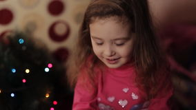 Little girl decorating Christmas tree at home. Little girls in comfortable home clothes sitting on floor in beautiful Christmas decorations. Two little sisters stock video footage