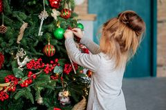A little girl is decorating a Christmas tree in the house. The concept of a Merry Christmas, holiday, family.  Royalty Free Stock Images