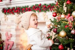 Little girl decorating christmas tree near fireplace. Little girl wearing cap, decorating christmas tree near fireplace. Concept of celebrating New Year and Royalty Free Stock Photo