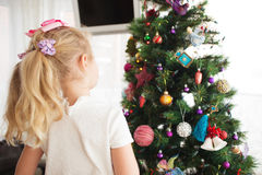 Little girl decorating Christmas tree before new year's eve. Royalty Free Stock Image