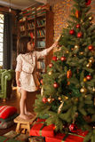 Little girl  is decorating christmas tree Royalty Free Stock Photo