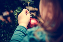 Little girl is decorating Christmas Tree in retro filter effect Stock Image