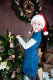 Little girl decorating christmas tree with toys and baubles. Royalty Free Stock Photo