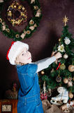 Little girl decorating christmas tree with toys and baubles. Royalty Free Stock Image