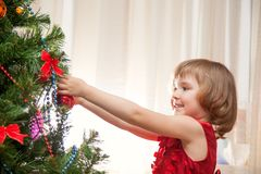 Little girl decorating christmas tree with toys royalty free stock images