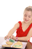 Little girl decorating cookies Royalty Free Stock Photos