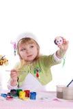 Little girl decorating easter eggs. Over white Royalty Free Stock Photo