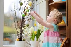 Little girl decorating home for Easter Stock Images