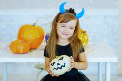 Little girl in demon costume playing with pumpkins Royalty Free Stock Image