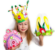 Little girl demonstrating her craft works, Easter bonnets Stock Photo