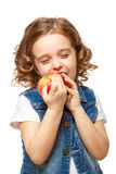 Little girl in a denim jacket holding a red apple. Royalty Free Stock Images