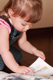 Little girl in denim jumpsuit reads book Stock Photography