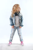 Little girl in denim suit and pink sneakers looking away Royalty Free Stock Image