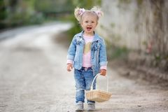 A little girl in a denim suit walks alone in a spring park with a wicker basket in her hands. Outdoor summer portrait of a little girl in the countryside on a royalty free stock photos