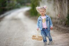 A little girl in a denim suit walks alone in a spring park with a wicker basket in her hands. Outdoor summer portrait of a little girl in the countryside on a stock photo
