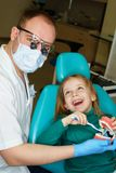 Little girl in dental clinic. Dentist explains rules of brushing teeth to little girl, holding mock jaw. Girl holding toothbrush. Lesson of oral hygiene stock photography