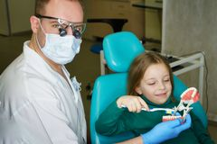 Little girl in dental clinic. Dentist explains rules of brushing teeth to little girl, holding mock jaw. Girl holding toothbrush. Lesson of oral hygiene. Dentist stock photos