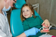 Little girl in dental clinic. Dentist explains rules for brushing your teeth little girl. He is holding toothbrush stock photo