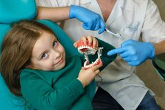 Little girl in dental clinic. Dentist explains rules of little girl brushing teeth, holding toothbrush and model of jaw. Girl fooling around. Lesson of oral royalty free stock photos