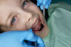 Little girl in dental clinic. Dentist hands with medical instruments. Little girl sits in dental chair with her mouth open. Routine inspection royalty free stock photo