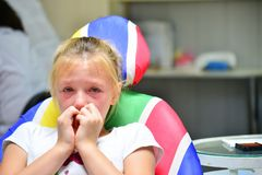 A little girl at the dentist is crying with tears at a doctor`s appointment while treating a tooth. A little girl at the dentist is crying with tears at a stock photography