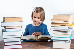 Little girl with a book on a white background. Little girl at a desk with a book learning on a white background Royalty Free Stock Photography