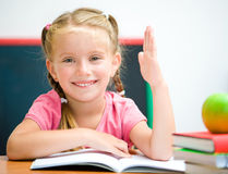 Little girl at the desk raised her hand Royalty Free Stock Photo
