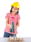 Little Girl Destroy Chess With Drill III. Concept image of little girl destroying a stone chess set with power drill stock photography