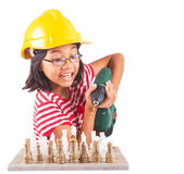 Little Girl Destroy Chess Set WIth Drill II. Concept image of little girl destroying a stone chess set with power drill royalty free stock image
