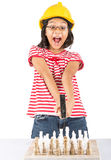 Little Girl Destroy Chess Set WIth Hammer II. Concept image of little girl destroying a stone chess set royalty free stock photo