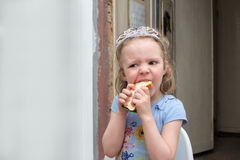 Little girl in diadem hungrily bites sandwich Stock Images