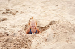 Little girl digging in the sand on the beach. Little girl goes along the coast stock photography