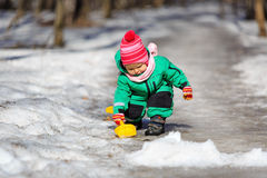 Little girl digging snow in winter Royalty Free Stock Image