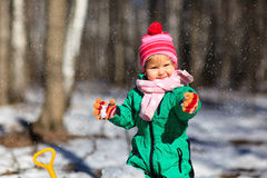 Little girl digging snow in winter Stock Photo