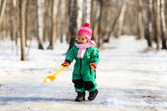 Little girl digging snow in winter Stock Images